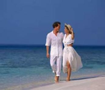 Honeymooners Enjoying A Walk Along The Beach